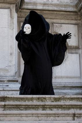 Eine Karnevalsfigur mit schwarzer cappuccio