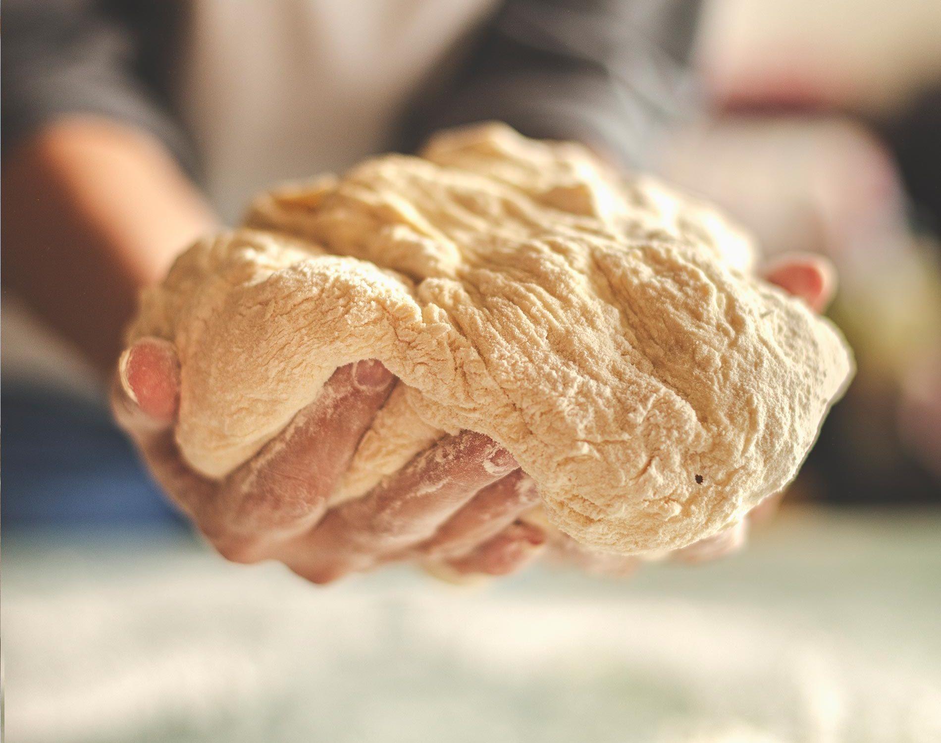 Pizzateig in der Hand